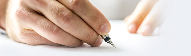 Close-up of a hand writing on white paper with a fountain pen